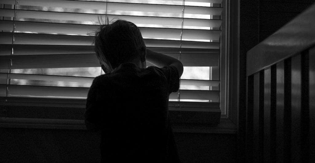 fotografía en blanco y negro de un niño asomado a la ventana